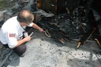A man sifts through burnt debris