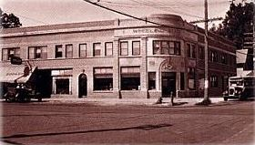 A historical photo of a building on the corner.
